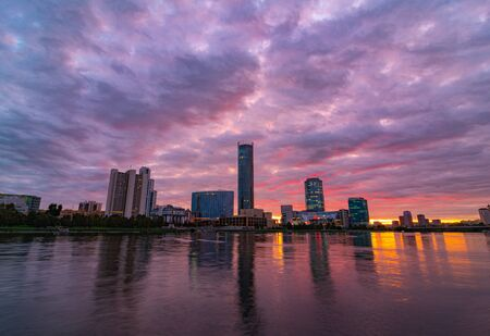Beautiful purple and orange cloudy sunset at the city pond. Cityscape of Yekaterinburg, Russia with skyscrappers reflecting in water