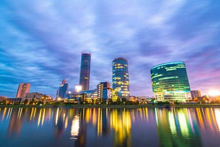 Night cityscape of Yekaterinburg, Russia with city lights reflecting in water of city pond