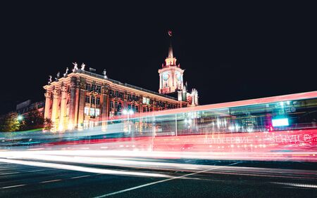 Light trails of passing cars in front of Yekaterinburg city hall at night with dark sky 写真素材