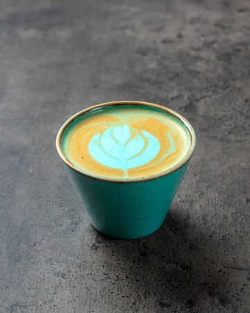 Close up of turquoise colored capuccino in beautiful greenish-blue cup with latte art on concrete gray background
