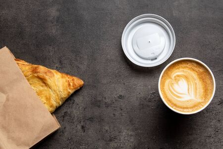 Samsa in paper envelope and cappuccino in paper cup on concrete gray background top view
