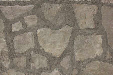The texture of the walls made of stones bonded with cement. Stock Photo