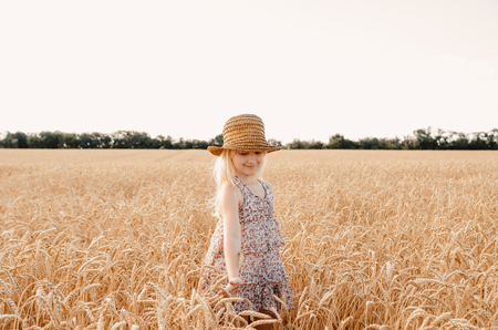 Happy child in autumn wheat field. Beautiful girl with white hair in a straw hat with ripe wheat in hands Stock fotó