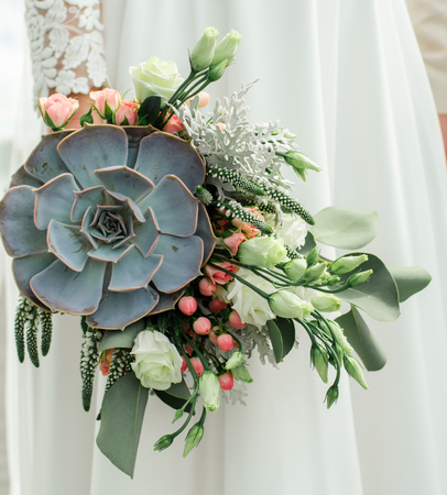 Wedding bouquet, exclusive, rich design Bride holding the wedding bouquet, close-up. Stock Photo