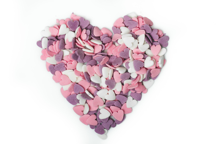Color sugar sprinkles heart shape, ornament for pie and bakery products, pink heart on white isolated background.