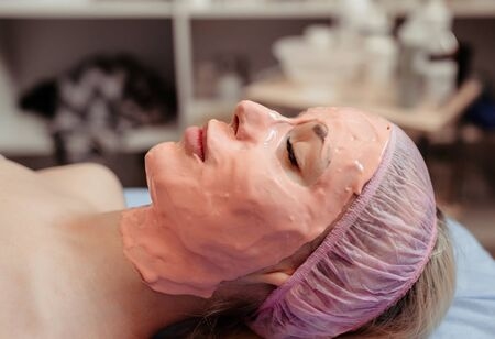 Woman with peel off face mask on her fase.
