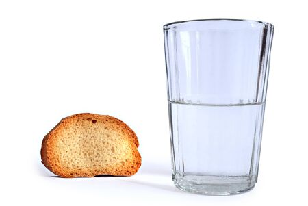 dry slice of bread and glass with water isolated photo