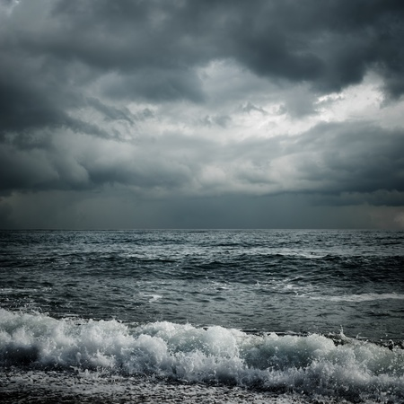 thunder storm: dark storm clouds and waves on the sea