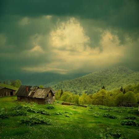 신비의 산 풍경입니다. 그린 밸리에있는 오래 된 나무 오두막 어두운 구름에서 빛의 광선 스톡 콘텐츠