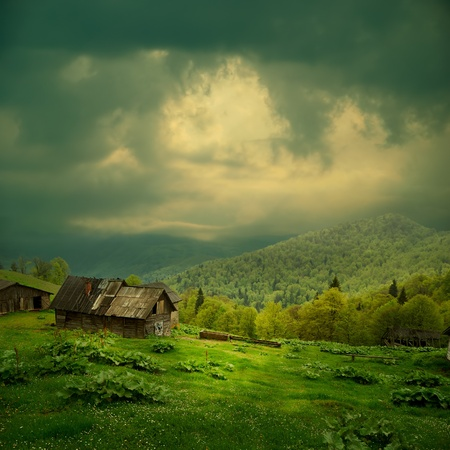 mystical forest: Mystery mountain landscape. Ray of light in dark clouds over the old wooden shack in green valley