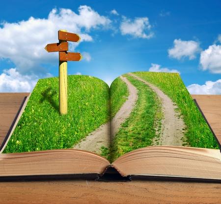 kouzelná kniha se silnicí uvnitř a ukazatel na pozadí oblohy Reklamní fotografie