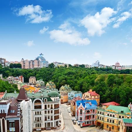 Vícebarevné domy mezi zelenými stromy a modrou oblohu. Panoramatický pohled z kopce. Umístěn v Kyjevě, na Ukrajině téměř v centru města.