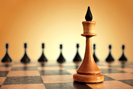chess king in focus and pawns on blurred background Stock Photo