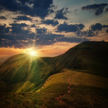 peak of the hill with pathway and mountain sunset rays on cloudy sky Stock Photo