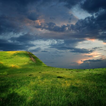 meadow and majestic sky with clouds over the green hills Stock Photo - 13736701