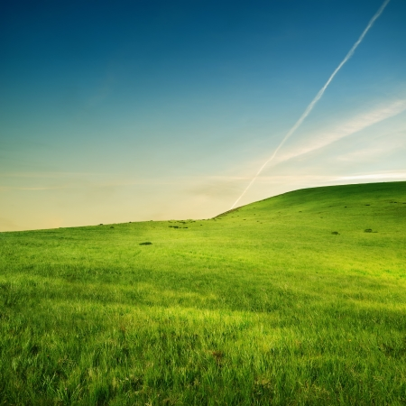 trace of airplane on the sky over green hills Stock Photo