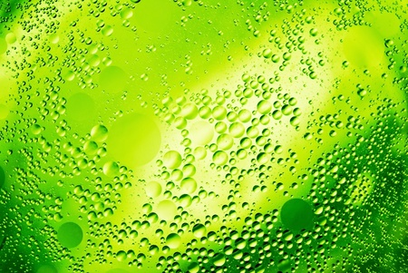 drops of oil and on green water, abstract background