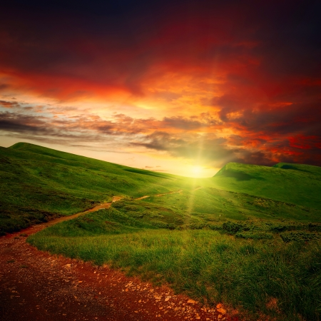 fantasy landscape: parth through a mystery mountain meadow to horizon with sunset clouds Stock Photo