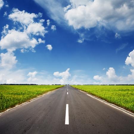 �horizon: carretera de asfalto a trav�s del campo verde y las nubes en el cielo azul en d�a de verano