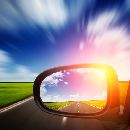 car side: car mirror with blue sky above road and blurred motion