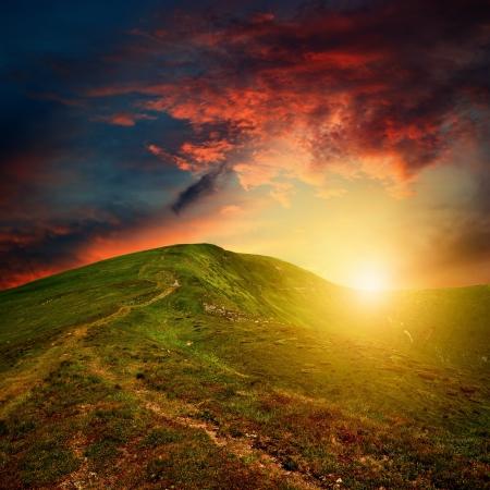 úžasné horské slunce s červenými mraky nad zeleném kopci