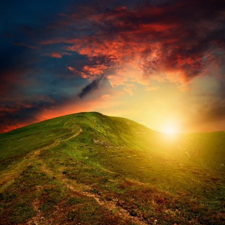 amazing mountain sunset with red clouds over the green hill
