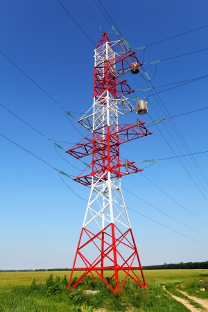 Pylon of power line in the field with transformer or inductance coil on cables  Red and white metal construction on blue sky background Stock Photo - 21172470