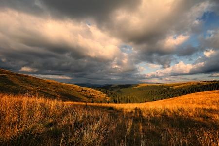 Mraky nad horského údolí a vzdálené lesa při západu slunce