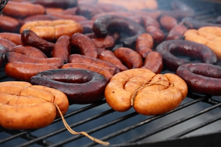 grilled sausages and smoke outdoors in selective focus photo