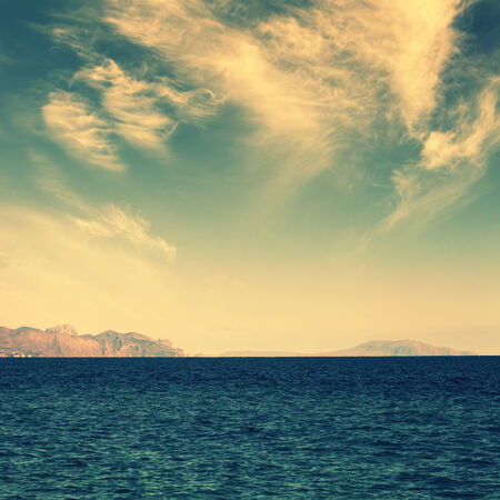 sea with island on horizon and clouds on sky, vintage colors