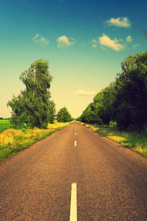 長いアスファルトの道路と緑の木とレトロな色