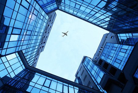 office buildings as a frame with blue sky and airplane Stockfoto