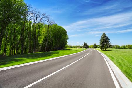 Asphalt road between trees and grass on roadside. Summer landscape with blue sky Stockfoto