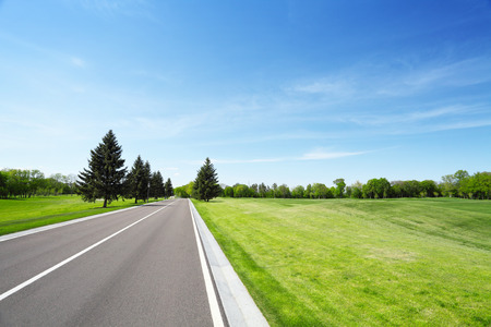 speedway park: Asphalt road and grassy green field. Summer landscape with blue sky Stock Photo