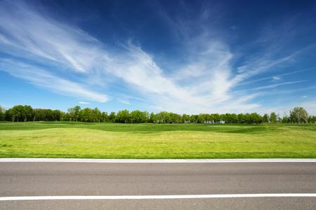 木、アスファルトの道路、背景に青い空と緑の草原