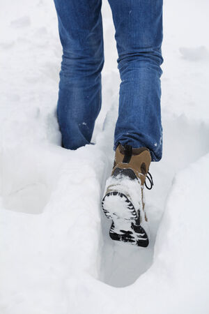 Man walks through the deep snow in a winter day. Foot in selective focus
