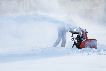 snow day: man with a snow blowing machine working in winter day Stock Photo