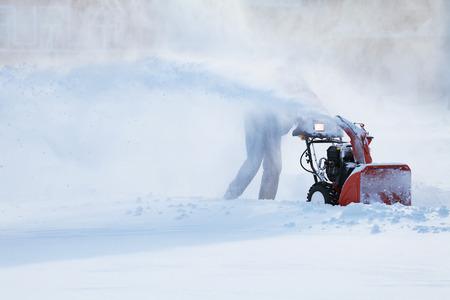 Mann mit einer Schnee Blasmaschine in Wintertag Arbeits