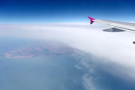 airplane wing over the clouds with sea water and land at bottom Stock Photo