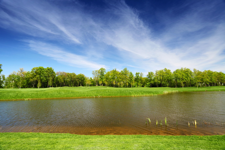 blue green landscape: Green meadow and calm river. Blue sky with clouds above the trees. Tranquil summer landscape Stock Photo