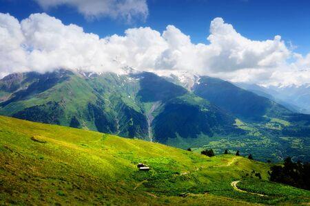 Horská krajina s malým dřevěné chatrči v zeleném údolí. Bílé mraky na modré obloze v letní den