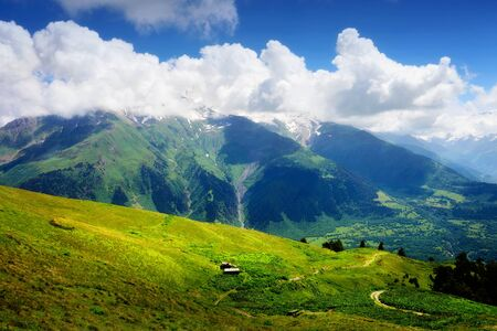 Mountain landscape with small wooden shack in green valley. White clouds on blue sky in summer day