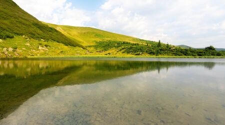 mere: mountain lake with stones on bottom, green hills reflected in water