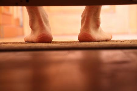 pies masculinos: Hombre Foto pies descalzos de debajo de la cama, enfoque selectivo