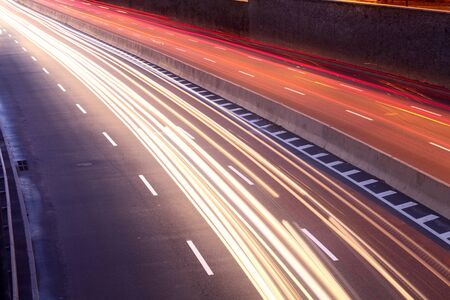 to bend: light trails of moving cars on city street Stock Photo