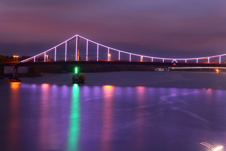 Bridge in Kiev at night, illuminated with colorful lights. Reflection in water of river Reklamní fotografie