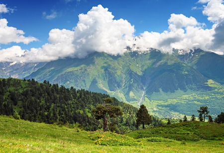 blue green landscape: Beautiful landscape of Caucasus mountains. Snow-capped peaks and green valley below. Blue sky with clouds above