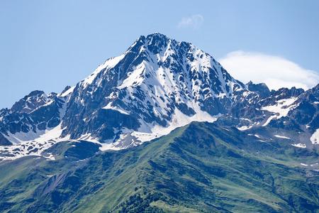 svaneti: Mountain peak in snow and green hills below. Svaneti, Georgia