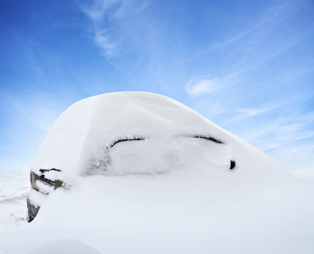 inclement: Car under deep snow in winter day after snowfall. Blue sky on background