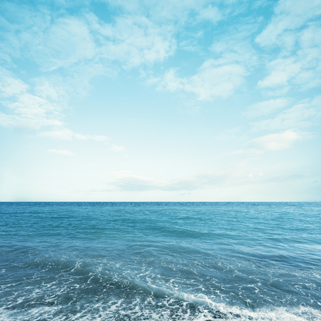 Light turquoise sea water with sky and fluffy clouds. Summer seascape